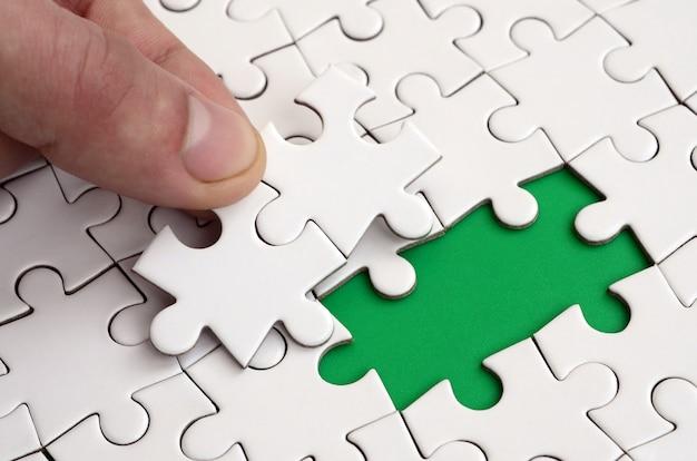 La mano umana riempie gli ultimi elementi mancanti della superficie dal puzzle. Foto Premium
