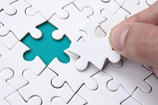 La mano umana riempie gli ultimi elementi mancanti della superficie dal puzzle Foto Premium
