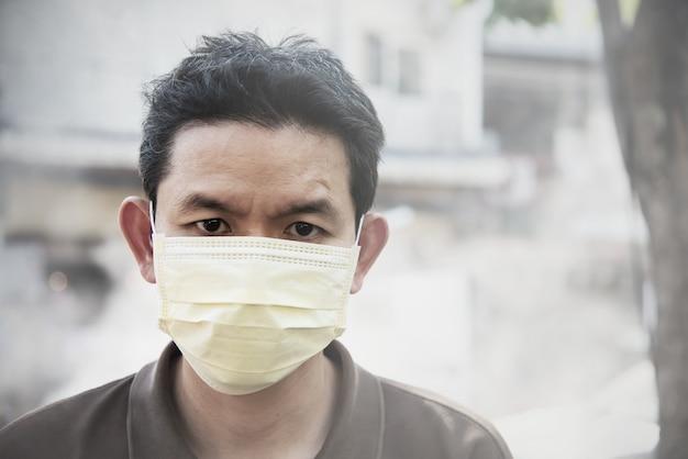 La maschera da portare dell'uomo protegge la polvere fine nell'ambiente dell'inquinamento atmosferico Foto Gratuite