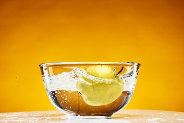 La mela cade nel bicchiere frutta succosa in acqua. Foto Premium