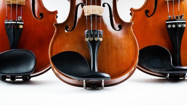 La metà del lato anteriore del primo piano di tre violini ha messo sopra il fondo, mostra il dettaglio e la parte del violino Foto Premium