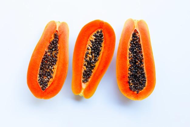 La metà della frutta matura della papaia con i semi isolati su fondo bianco Foto Premium