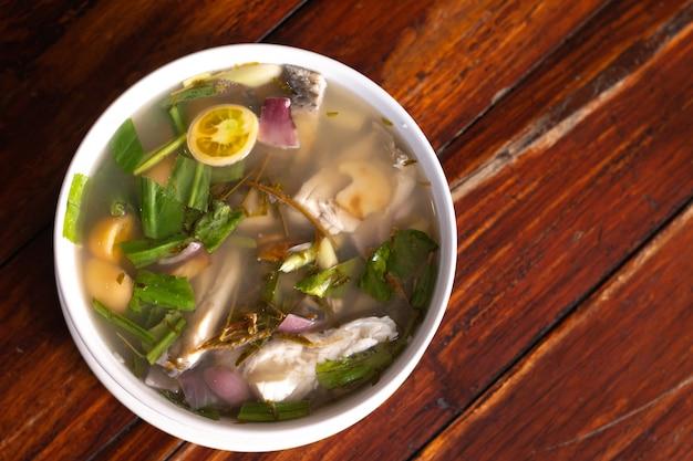 La minestra di pesce piccante condita con citronella e calce è servito sulla tavola di legno Foto Premium