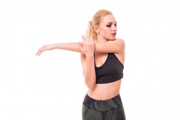 La modella bionda magra fa diversi esercizi in studio vestita in abiti sportivi scuri Foto Gratuite