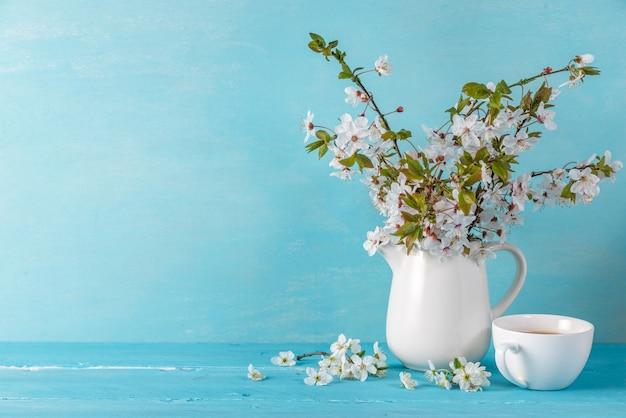 La natura morta con un bello fiore di ciliegia della molla fiorisce, tazza di caffè sulla tavola di legno blu con lo spazio della copia Foto Premium