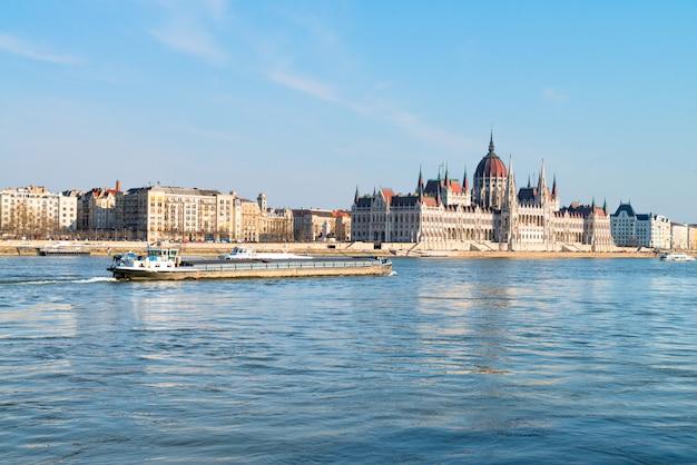 La nave da carico passa l'edificio del parlamento nel centro di budapest Foto Premium