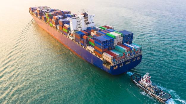 La nave porta-container che arriva nel porto, la nave porta-container e la barca del rimorchiatore che vanno al porto marittimo, l'importazione logistica di affari importano il trasporto ed il trasporto, vista aerea. Foto Premium