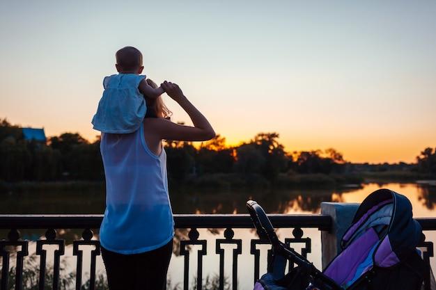 La neonata che si siede sulle spalle di sua mamma e ammira il paesaggio. Foto Premium
