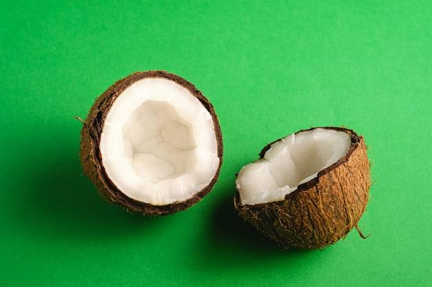 La noce di cocco fruttifica sulla superficie normale verde, il concetto tropicale dell'alimento astratto, vista di angolo Foto Premium