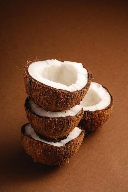 La noce di cocco impilata fruttifica sulla parete normale marrone, il concetto tropicale dell'alimento astratto, vista di angolo Foto Premium