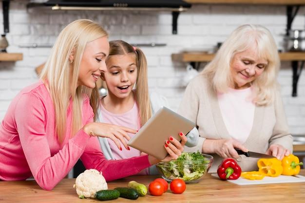 La nonna cucina e le donne usano il tablet Foto Gratuite