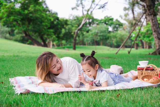 La nonna e la nipote asiatiche che mettono sul vetro verde sistemano all'aperto, famiglia che gode insieme del picnic nel giorno di estate Foto Premium