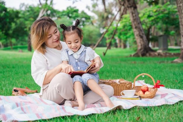La nonna e la nipote asiatiche che si siedono sul vetro verde sistemano all'aperto, famiglia che gode insieme del picnic nel giorno di estate Foto Premium