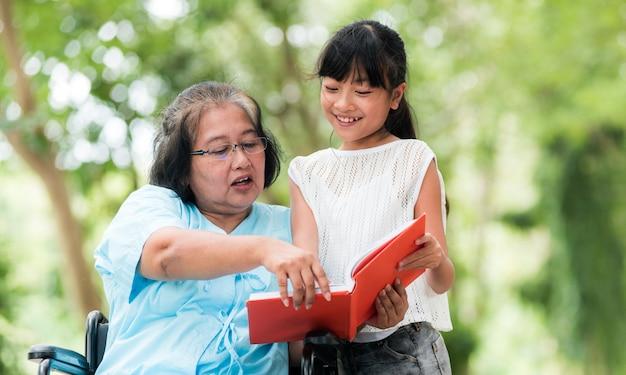 La nonna e la nipote hanno goduto di nel giardino. concezione asiatica della famiglia Foto Premium