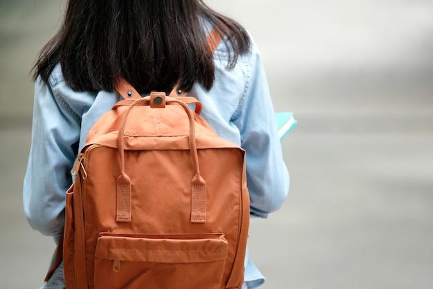 La parte posteriore dei libri della tenuta della ragazza dello studente e porta la borsa di scuola mentre cammina nel campus della scuola Foto Premium