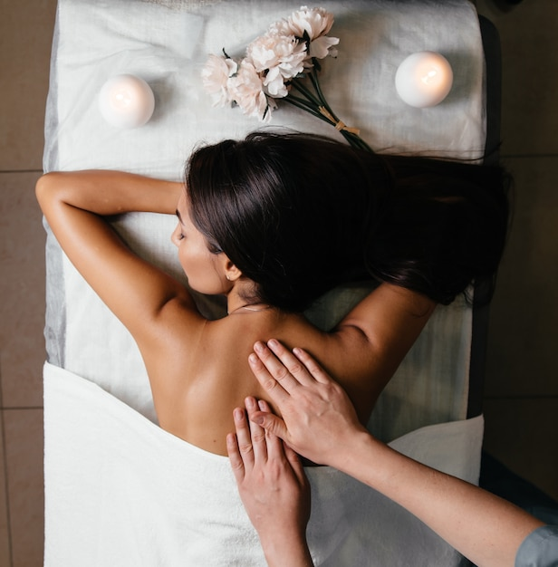 La parte posteriore del corpo della bella donna asiatica e l'unghia rosa su fondo grigio. Foto Premium