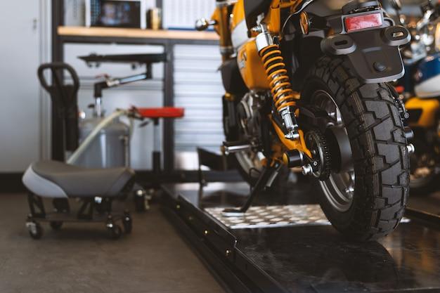 La parte posteriore delle moto classiche in piedi nel negozio di riparazione Foto Premium