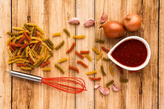 La pasta e l'ingrediente crudi con sbattono sulla tavola di legno Foto Gratuite