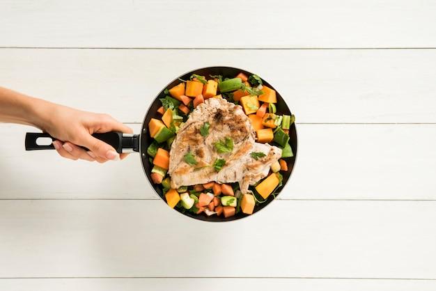 La persona che tiene il filetto di carne guarnito in padella Foto Gratuite
