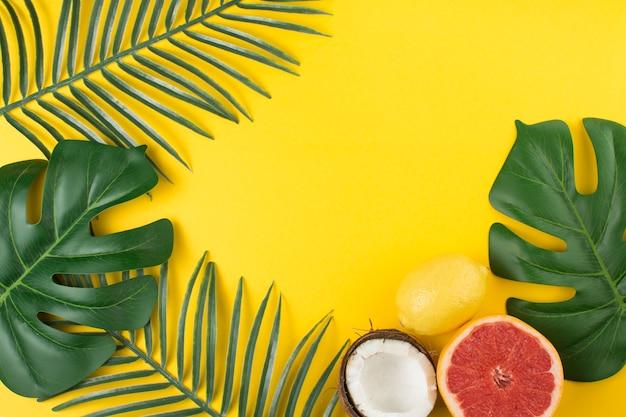 La pianta tropicale verdeggiante lascia vicino a frutta e cocco Foto Gratuite