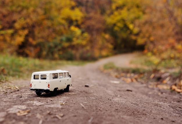 La piccola automobile bianca del giocattolo guida sulla strada degli alberi di giallo di autunno. Foto Premium