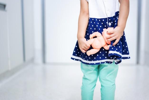La piccola bamboletta della tenuta del bambino ha paura di uscire la porta Foto Premium