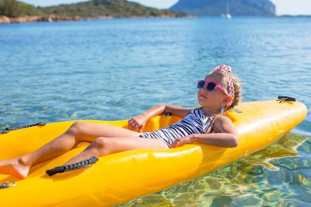 La piccola bella ragazza sveglia gode del kayak nel mare blu libero Foto Premium