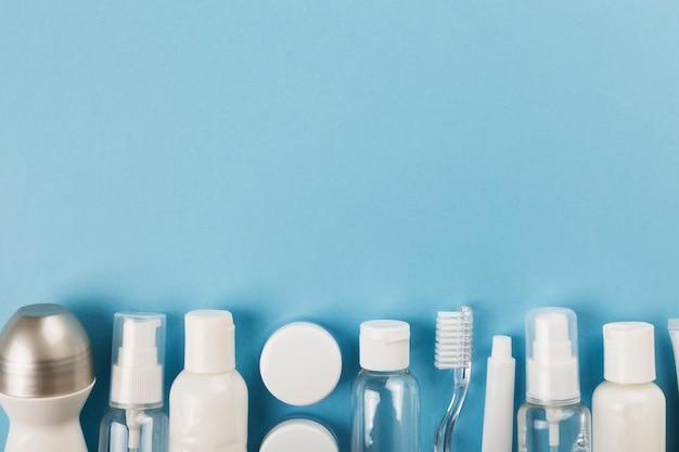 La piccola bottiglia di viaggio ha messo su fondo blu. vista dall'alto, copia spazio Foto Premium