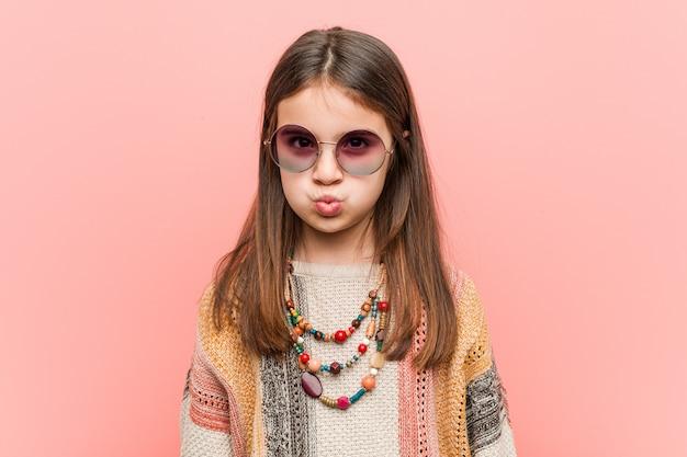 La piccola donna del hippie soffia le guance, ha espressione stanca. concetto di espressione facciale. Foto Premium