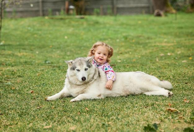 La piccola neonata che gioca con il cane contro l'erba verde Foto Gratuite