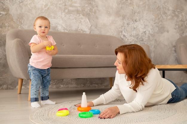 La piccola neonata raccoglie una piramide con i nonni al salone. la nonna gioca con la nipote sul pavimento Foto Premium