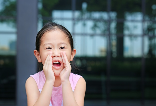 La piccola ragazza asiatica del ritratto del ritratto che si comporta e che grida tramite le mani gradisce il megafono. concetto di comunicazione Foto Premium