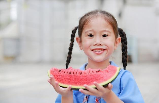 La piccola ragazza asiatica felice del bambino in uniforme scolastica gode di di mangiare l'anguria all'aperto. Foto Premium