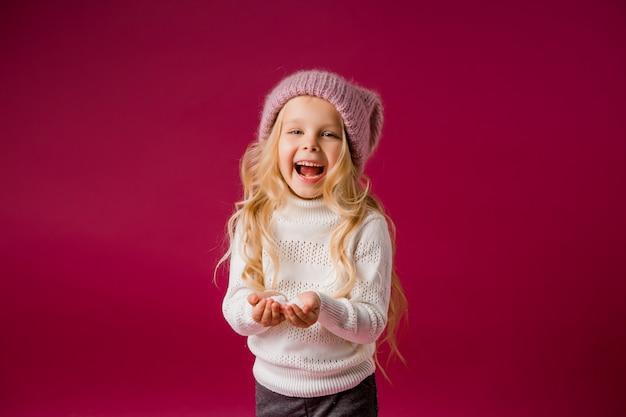 La piccola ragazza bionda con il cappello e il maglione tricottati gioca con la neve Foto Premium