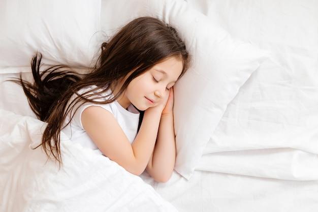 La piccola ragazza castana dorme dolcemente a letto con tela bianca. spazio per il testo. sonno del bambino sano Foto Premium