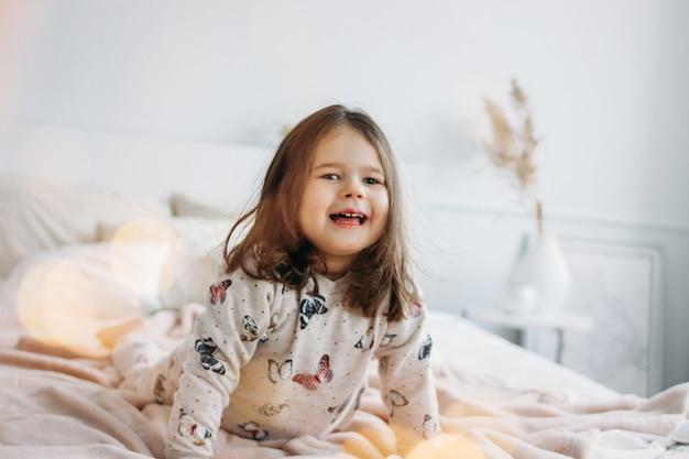 La piccola ragazza felice in pigiami accoglienti sul letto dei genitori nella casa Foto Premium