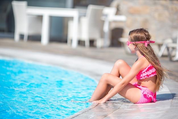 La piccola ragazza felice nella piscina all'aperto gode della sua vacanza Foto Premium