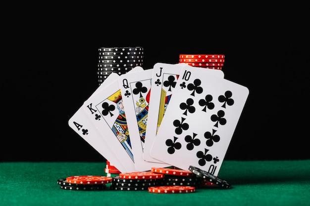 La pila dei chip del casinò e la carta da gioco di scala reale sulla tavola verde della mazza Foto Gratuite