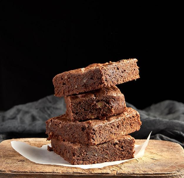 La pila di pezzi quadrati al forno di brownie al cioccolato agglutina sul tagliere di legno marrone Foto Premium