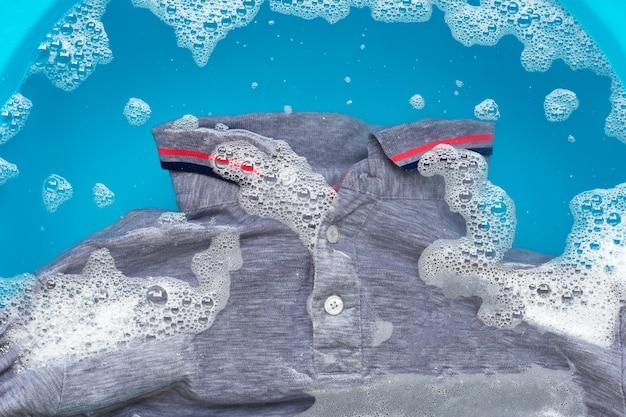 La polo grigia imbevuta di dissoluzione in acqua con detergente in polvere. concetto di lavanderia Foto Premium