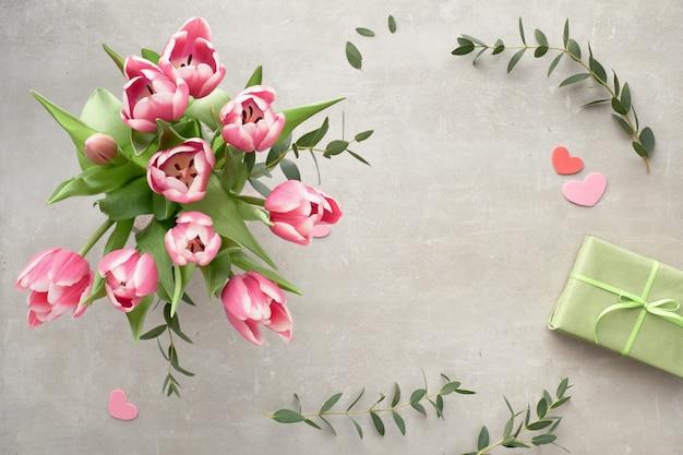 La primavera era piatta con un mazzo di tulipani rosa, foglie di eucalipto e scatole regalo Foto Premium