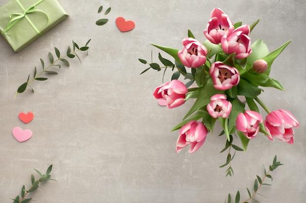La primavera piatta giaceva con un mazzo di tulipani rosa, foglie di eucalipto e scatole regalo su pietra Foto Premium
