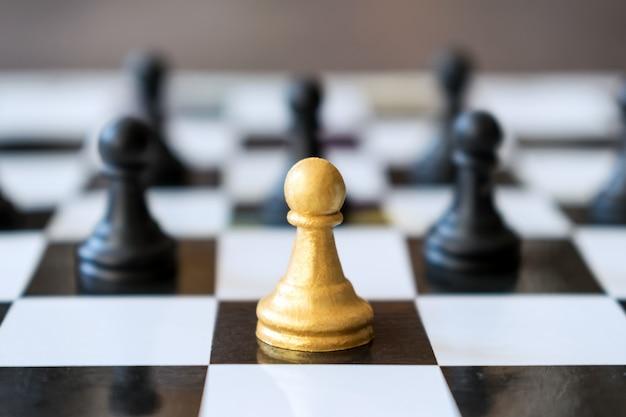 La principale pedina d'oro principale sta davanti alle normali pedine nel gioco degli scacchi Foto Premium