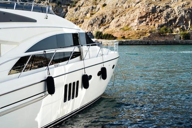 La prua di un lussuoso yacht bianco si trova sul molo in una piccola baia del porto. passamontagna crimea. Foto Premium