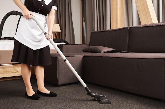 La pulizia della casa è la chiave per la produttività. colpo ritagliato di cameriera durante il lavoro, pulizia del soggiorno con aspirapolvere, rimozione di sporcizia e pasticcio vicino al divano. la cameriera è pronta a far brillare questo posto Foto Gratuite