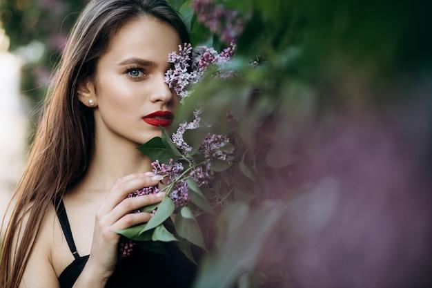 La ragazza affascinante si trova vicino a cespugli con fiori Foto Gratuite