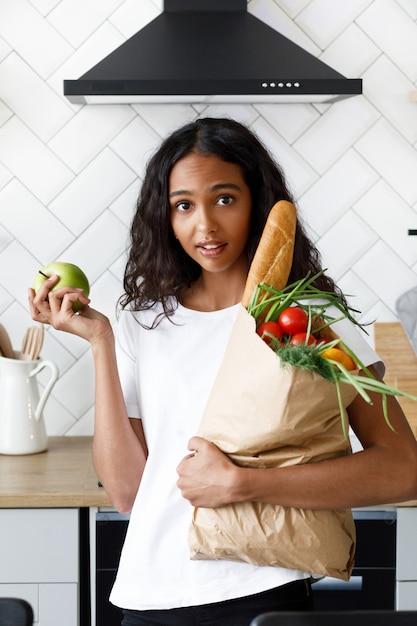 La ragazza africana sta sulla cucina in possesso di un sacco di carta con generi alimentari e ha sorpreso lo sguardo Foto Gratuite