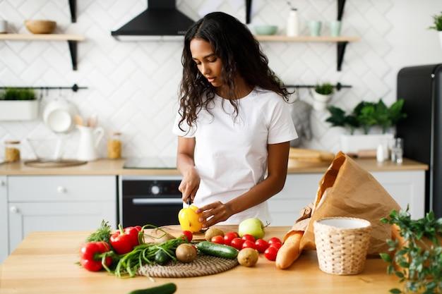La ragazza africana sta tagliando un peperone giallo sullo scrittorio della cucina e sul tavolo sono i prodotti di un supermercato Foto Gratuite