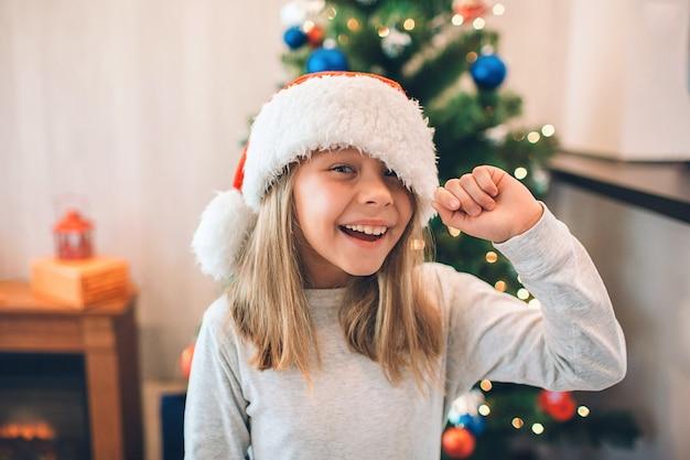 La ragazza allegra e positiva tiene il bordo del suo cappello di natale. Foto Premium