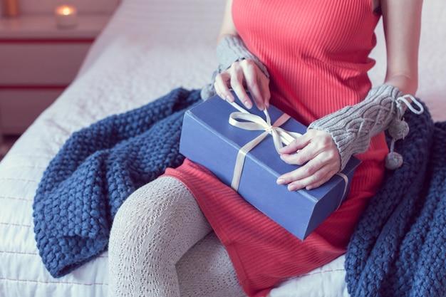 La ragazza apre un regalo mentre è seduta sul letto Foto Premium